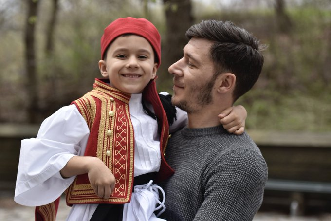 Father holding his child, who is wearing traditional Greek clothing.