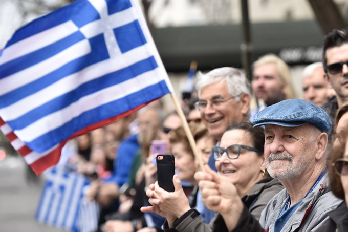 Crowd watching a parade. Someone waves a Greek and American flag together