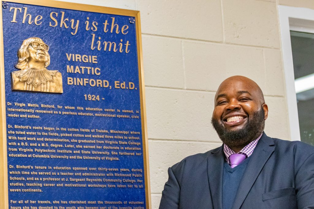 Rodney Robinson stands beside a sign that details the biography of Virgie Binford, Ed.D., for whom the education center where he teaches is named.