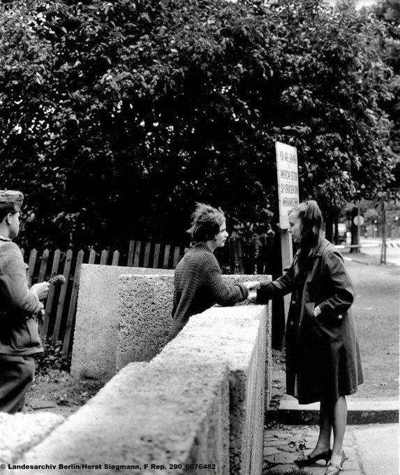 Zwei Mädchen an der noch nicht fertiggestellten Berliner Mauer in Treptow in der Harzer Straße. Sie sprechen miteinander und fassen sich an. Etwas weggedreht steht ein Soldat. Er hat keine Pistole und kein Gewehr in der Hand, sondern eine Blume.