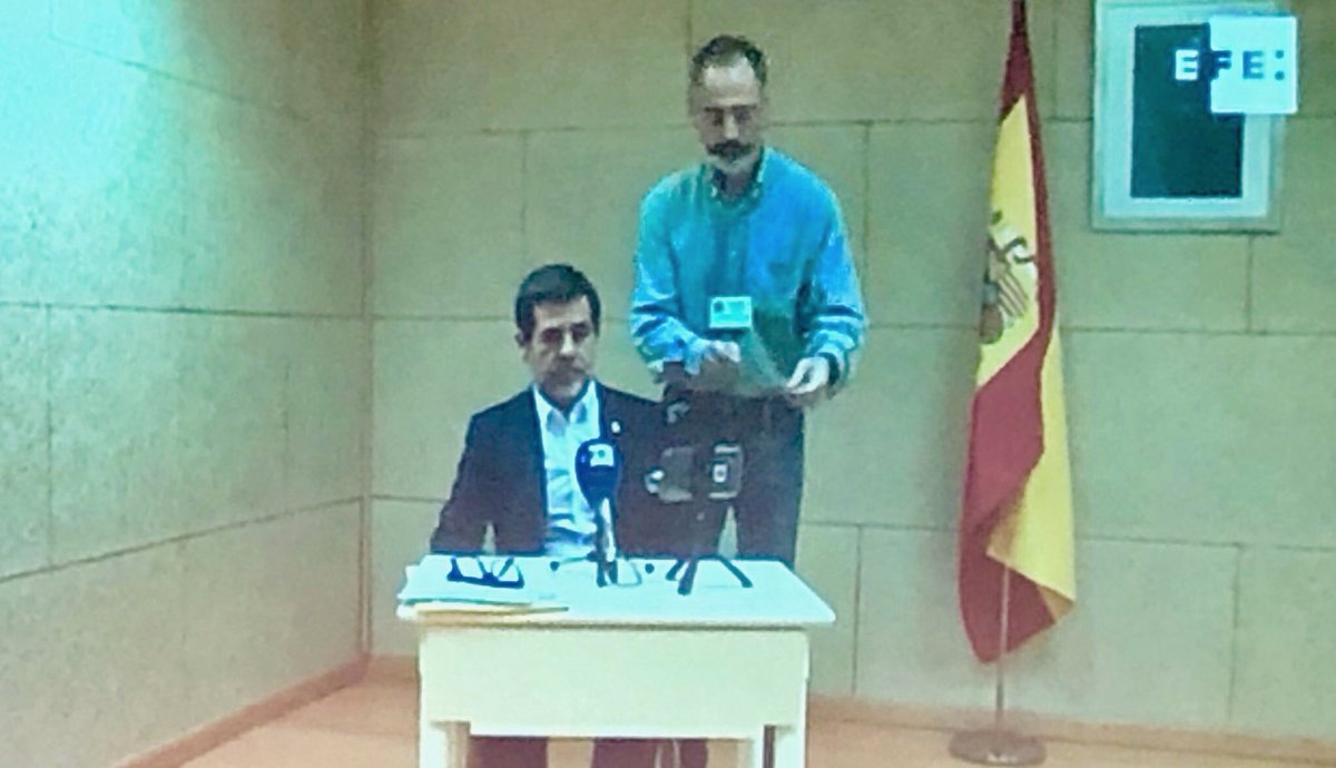 Spain shows one Catalan political prisoner @jordialapreso together with the Spanish flag and a photo of the King of Spain.