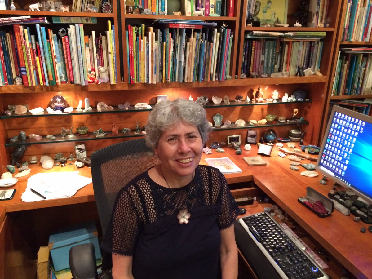 Marilyn Singer in her office, with desktop computer, bookshelves and souvenirs.