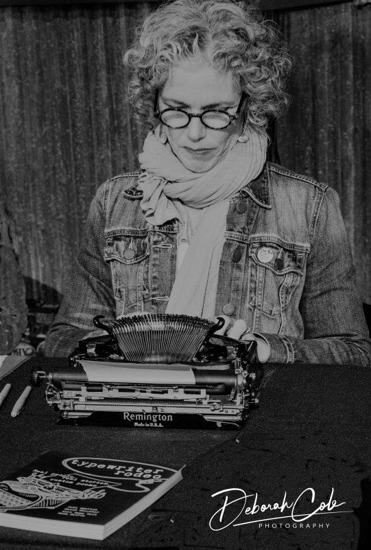 Liz Garton Scanlon at a manual typewriter.