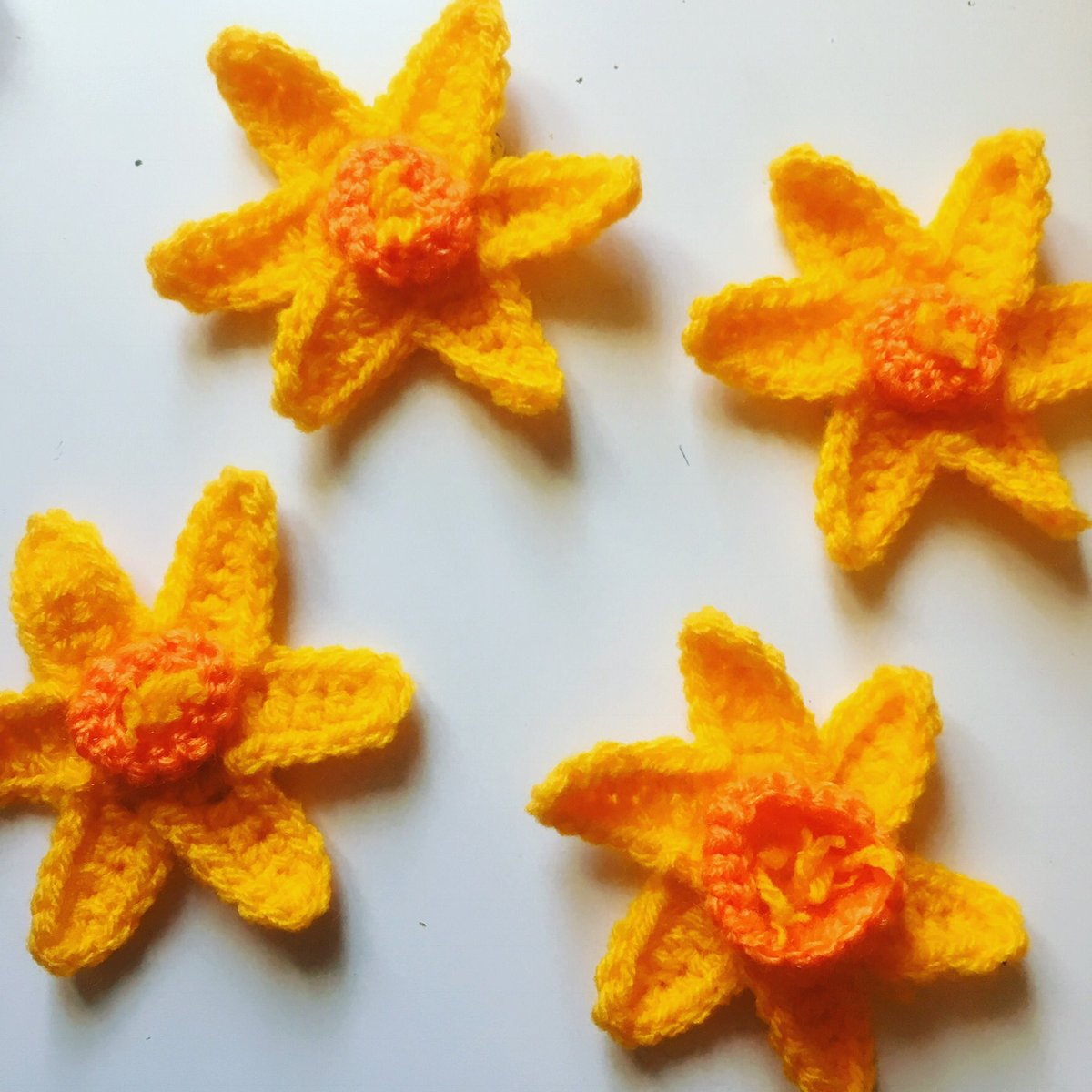 There are 4 yellow, crocheted daffodils with orange middles