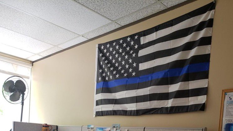 "A county in Oregon has agreed to pay a woman $100,000 in a settlement, after a coworker put up a ""Blue lives matter"" police flag pictured here! The woman claimed the ""Blue lives matter"" flag demeaned and insulted her and her ""Black Lives Matter"" movement! 😮😮"