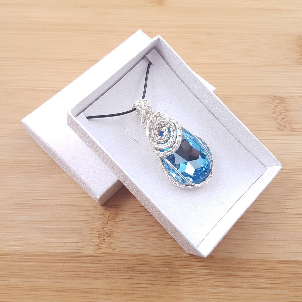 Light blue Swarovski pendant wrapped in silver wire in white box