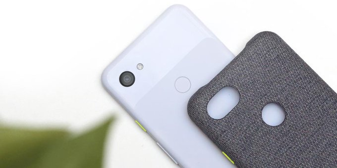 The Pixel3a rests on a white background with a grey phone case resting on top of the phone.