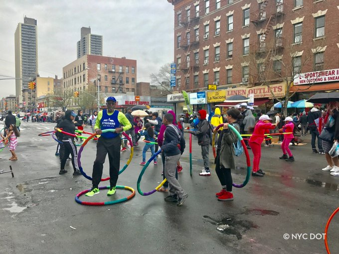 People hula hoop on a street closed to vehicles during Car Free Earth Day Uptown 2017
