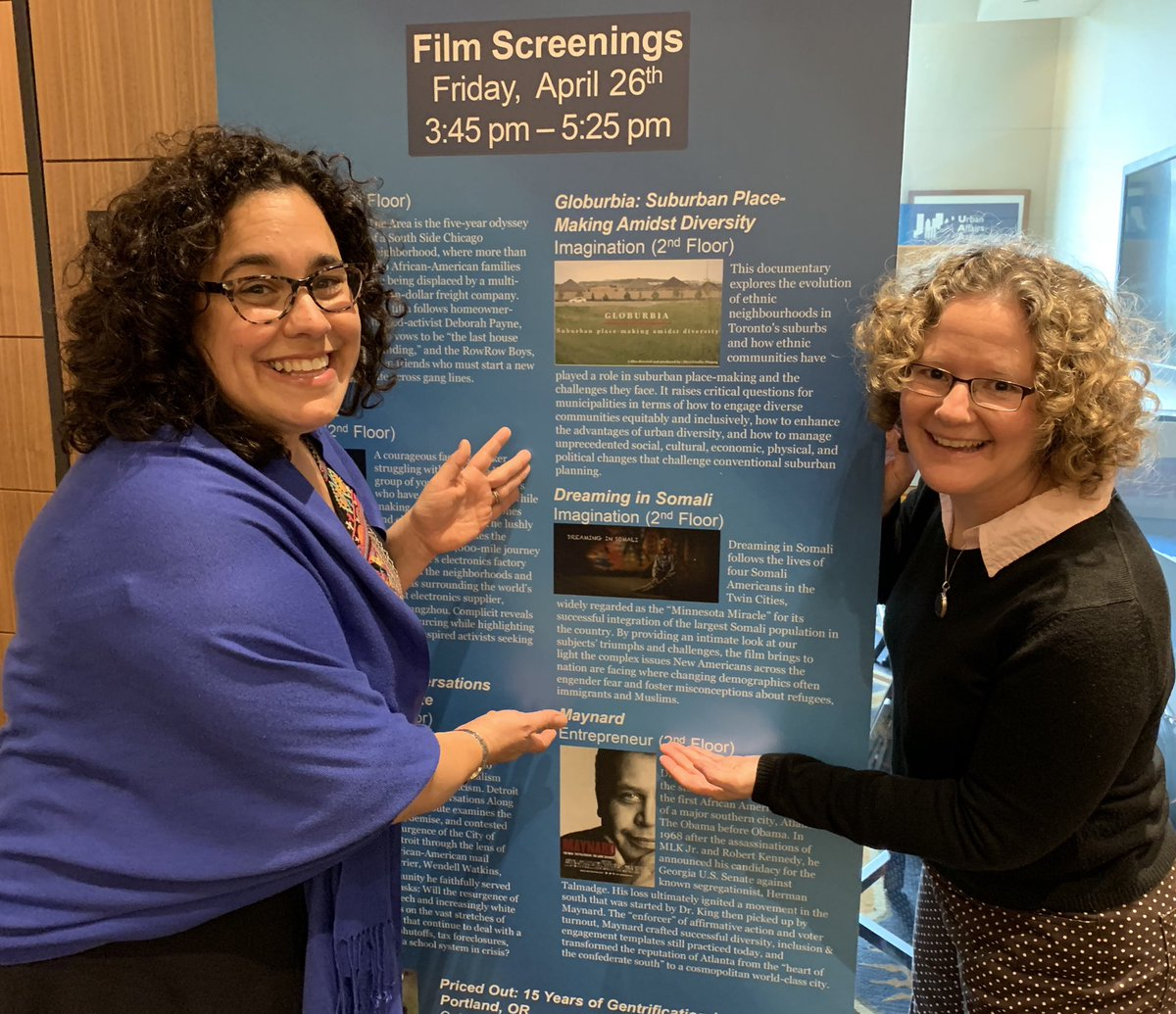 Photo to accompany bio of Chambers (who stands to the left) and Kalin (on the right). They are pointing to a large sign that lists the day's film screening, one of which is Dreaming in Somali.