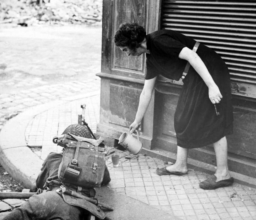 A French woman gives a British Bren gunner something to drink during the battle of Lisieux, August 1944. #WW2<br>http://pic.twitter.com/rAGvxJhePG