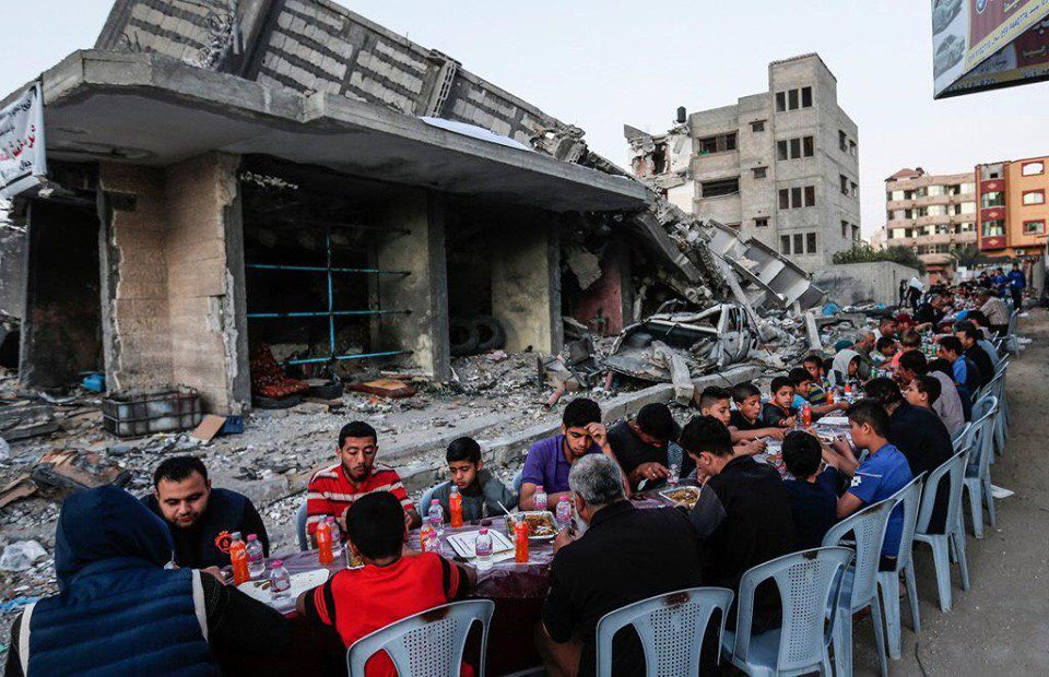 Palestinians hold iftar meals next to the buildings destroyed by Israeli warplanes in the last bombing.  #Gaza <br>http://pic.twitter.com/ggSfSpb4YO