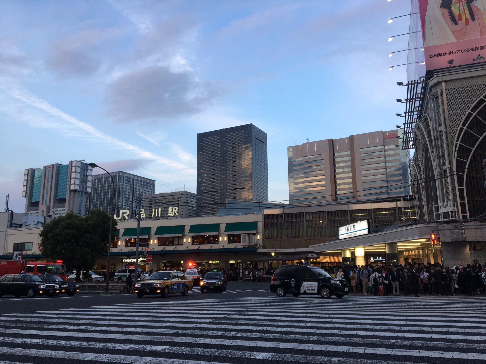 画像,品川駅前のロータリーに消防車3台とパトカー、赤橙のついたJRの車が停まってて上空でヘリが旋回中。日テレのテレビカメラもいて何かあった模様。 https://t.…