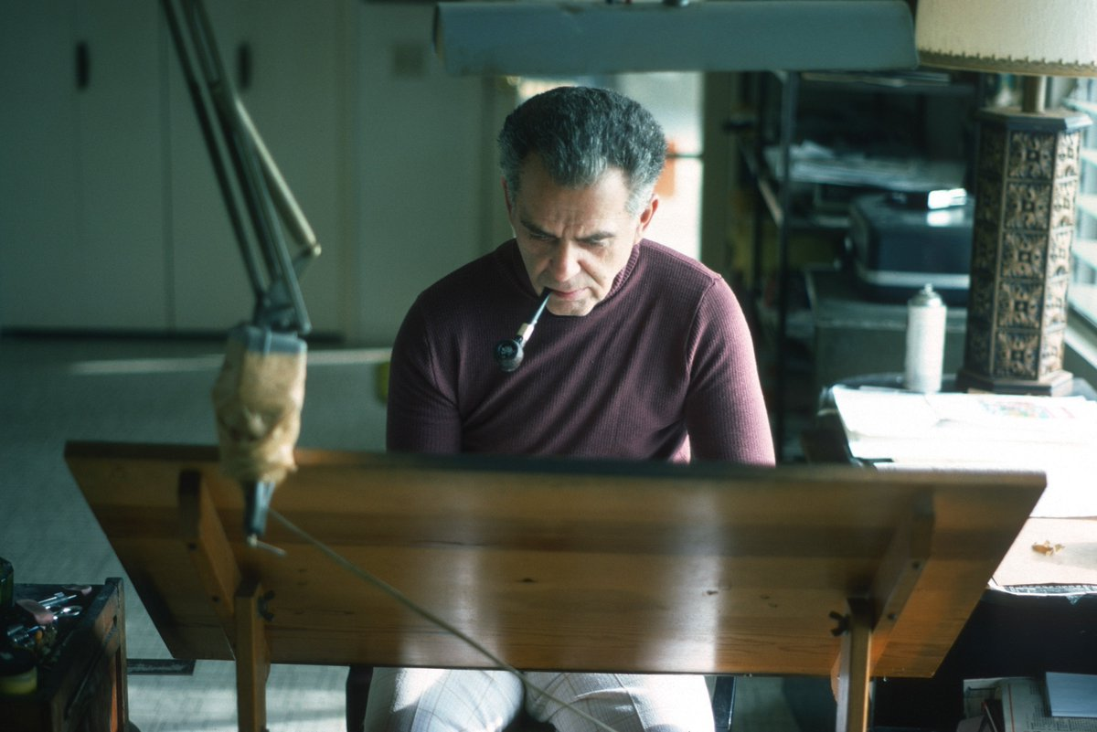 Jack Kirby at his drawing table creating universes