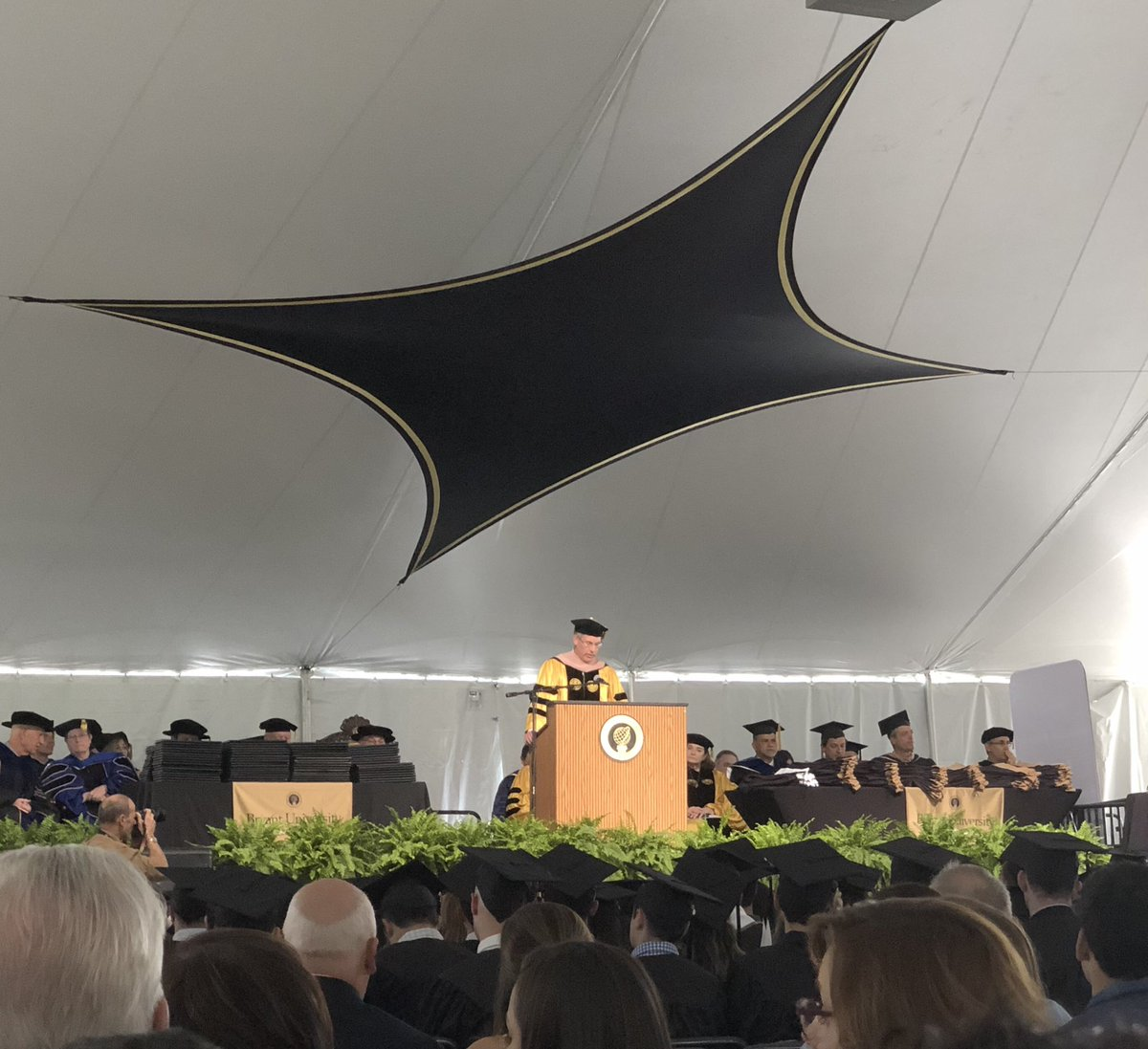 """Honorary degree recipient and @WashTrust CEO Edward """"Ned"""" O. Handy III gives the commencement address at Bryant's annual Graduate Programs Commencement. #BryantGrad2019"""