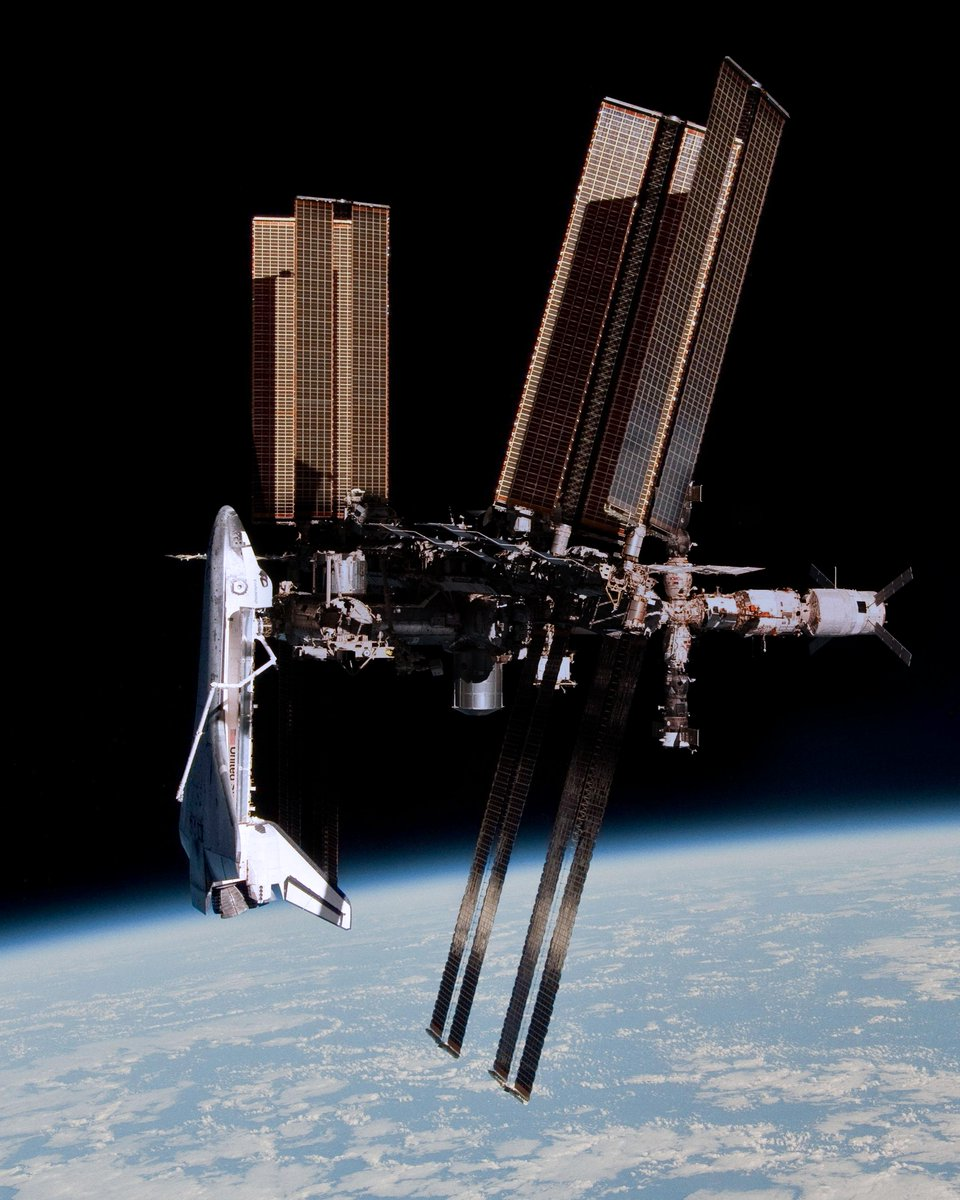 8 years ago today @astro_paolo caught the first-ever photo of a Space Shuttle docked to the ISS.  Because of a schedule change, for the first time in history, a Soyuz was departing ISS while a Shuttle was docked.<br>http://pic.twitter.com/qYPXtBtRjD