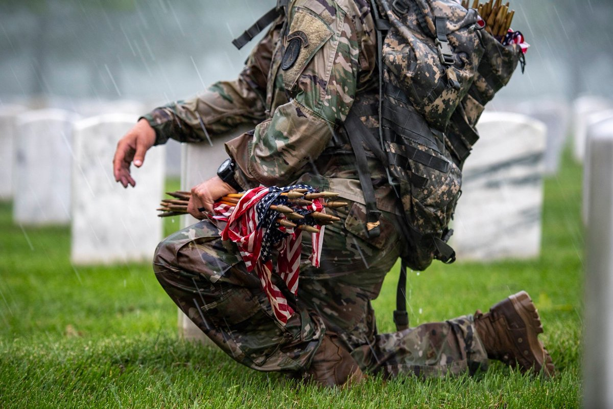 Soldier from @USArmyOldGuard takes a knee during a thunderstorm while participating in Flags-In at Arlington National Cemetery. For 55+ years, soldiers from The Old Guard have honored our nation's fallen by placing U.S. flags at gravesites. (U.S. Army photo by Elizabeth Fraser)
