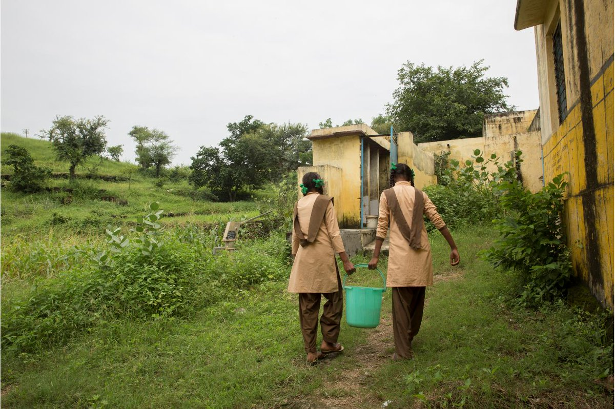 At an upper primary government school, girls carry heavy buckets of water to use the toilet facilities. School environments need to be equipped with clean and easily accessible water, sanitation and disposal facilities. #MHDay2019 #UnfinishedBusiness #ICPD25