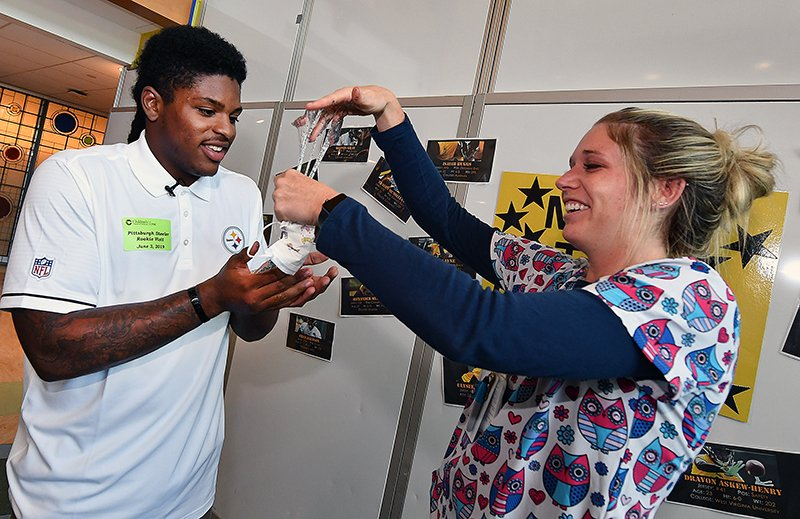 Pittsburgh Steelers No1 draft pick Devin Bush hands nurse Emily Johanson his slime while he takes a photo with another patient during their visit the Monday, June 3, 2019, at UPMC Childrens Hospital in Lawrenceville.