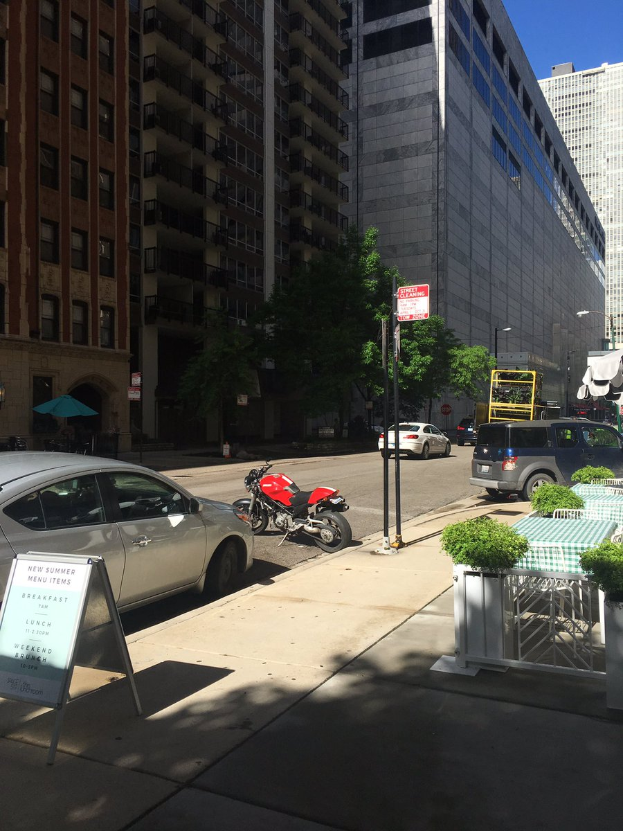 A truly Chicago moment: this Ducati parks in the same spot every day because the city put the no parking sign and the meter sign on two different poles, leaving a no-mans-land space just big enough for one bike.