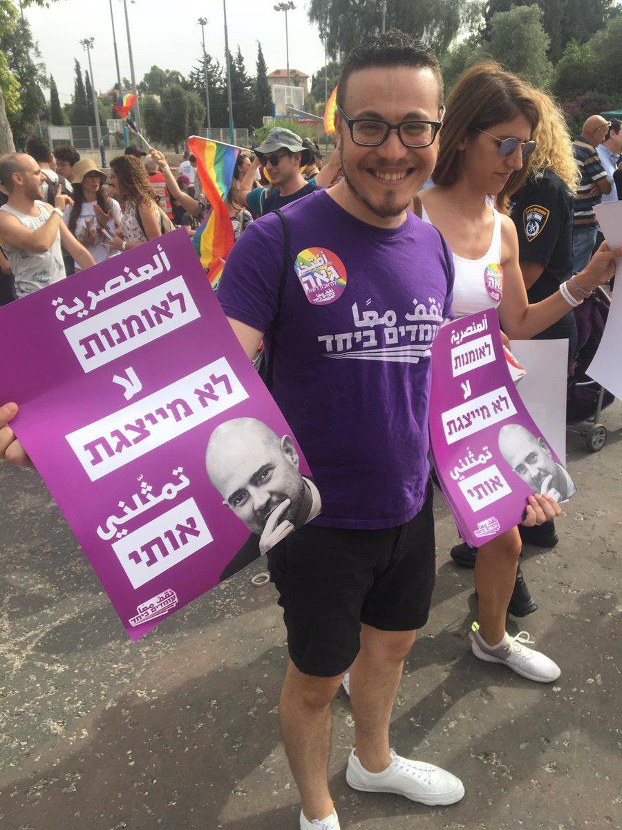 """מצעד הגאווה בירושלים: במקום מתקיימת חלוקת שלטים עליהם תמונה של שר המשפטים @AmirOhana, והכיתוב """"לאומנות לא מייצגת אותי"""" @akivanovick"""