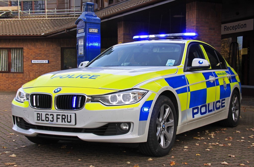 Stationary BMW police car with flashing blue lights, parked outside force hq.
