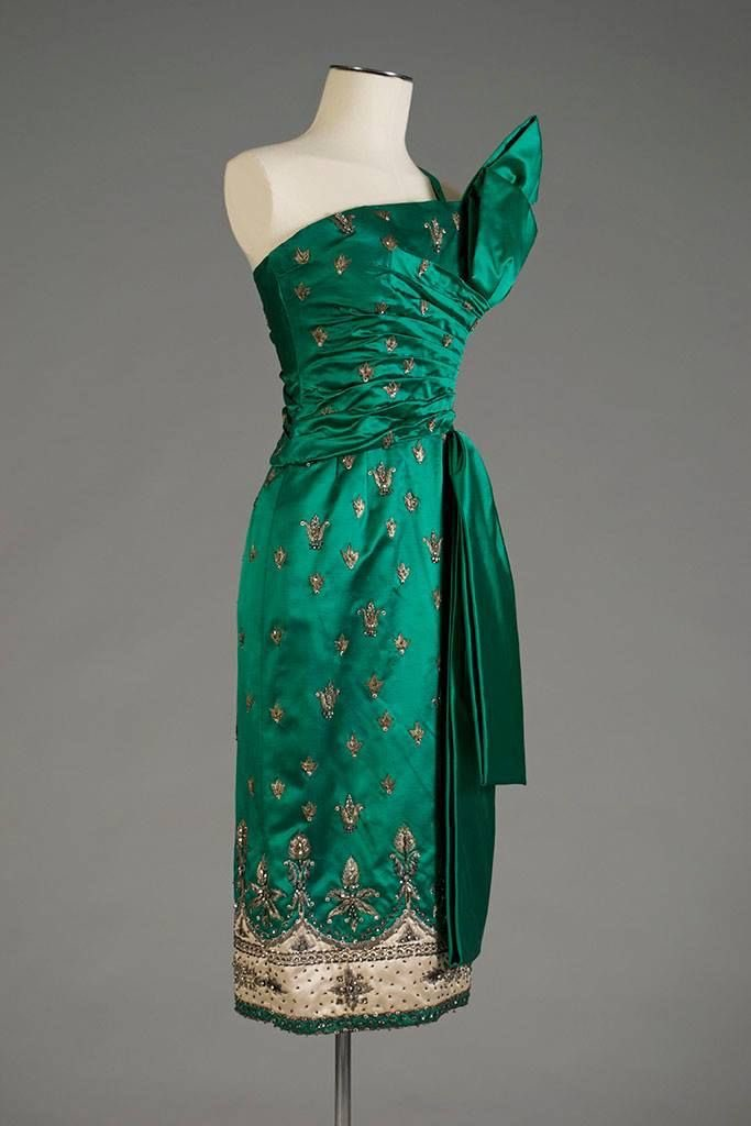 An unusual off centre construction in embellished emerald silk makes this late #1950s cocktail dress memorable. It also draws on the decorations and style of a #sari, inspired by Indian design @KSUMuseum #fashionhistory <br>http://pic.twitter.com/CjuhMRvIco