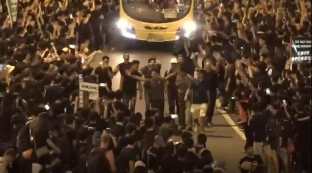 #extraditionbill #HongKongProtest 政府庁舎前。1台のバスを通しているところ。先頭に抗議者が歩いて、バスを先導しながら、みんなで道を開ける。脇にいる抗議者がみんなでバスに向かって拍手、手を振ってる。バスの中の客と一緒に喜び合ってる。みんな楽しそう!香港雨傘革命が帰ってきた!\(^o^)/