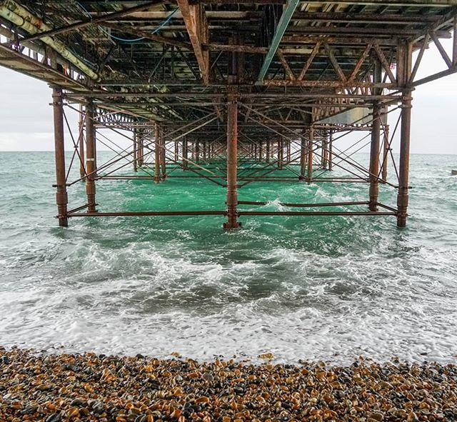 Under the pier. Its hard to believe that these rusty old weather beaten poles are what keep the Brighton pier standing. And yes, the water really was that green. After seeing the brown of the Thames for so long, it was quite lovely. #brightonrocks #brighton #brightonpier…
