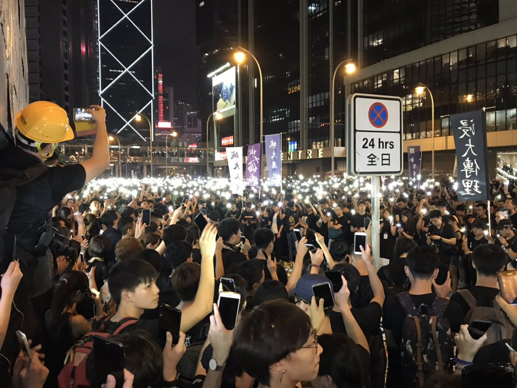 At a vigil for a man who police say jumped of metal scaffolding after unfurling a banner in protest of a proposed extradition bill, hundreds of people in the crowd hold up their phones