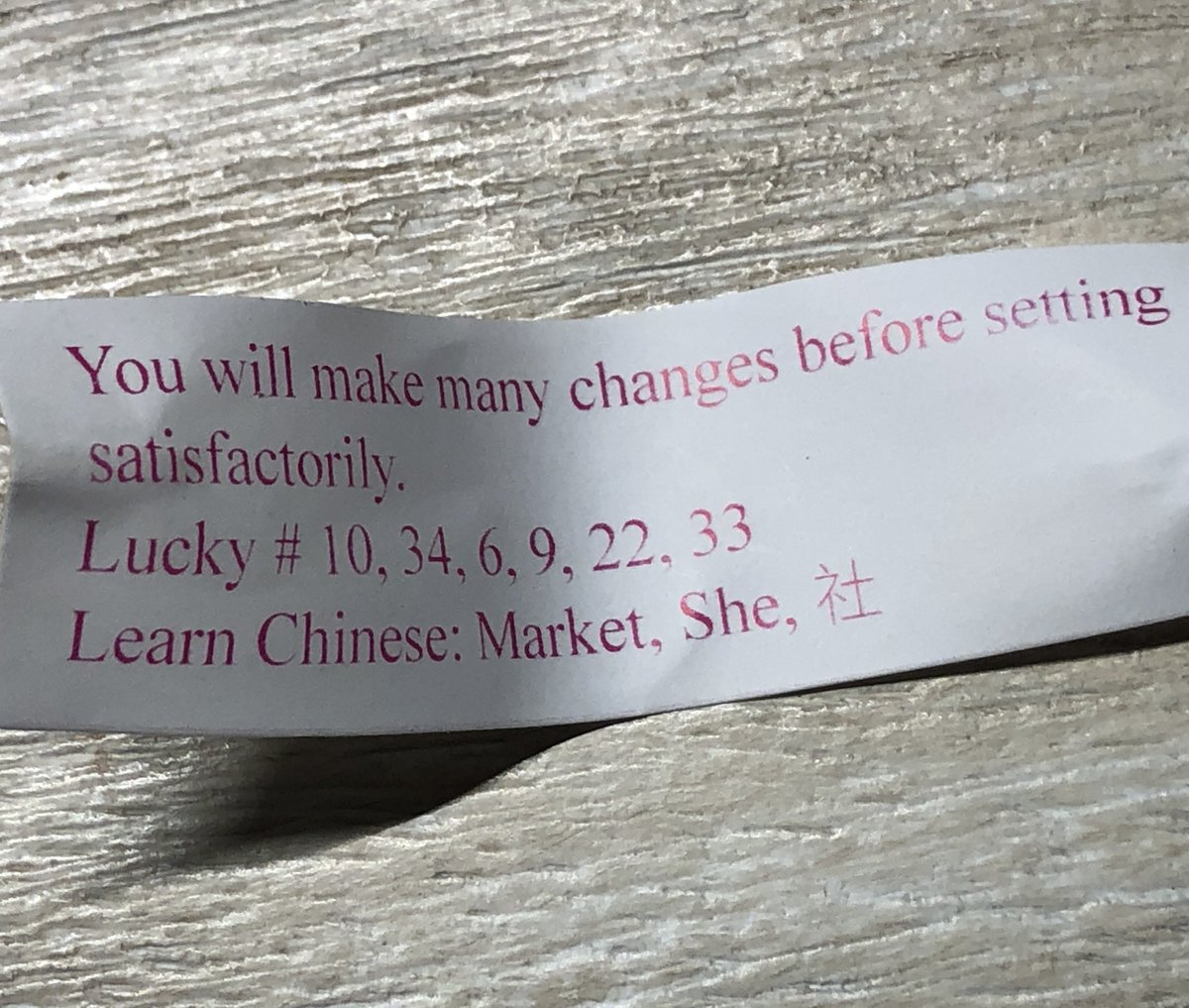 "Fortune cookie paper fortune that reads: ""You will make many changes before setting [sic] satisfactorily."""