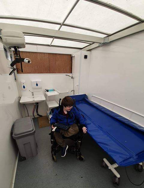 Eli is in his wheelchair sitting beside the bed changing bench inside Mobiloo.