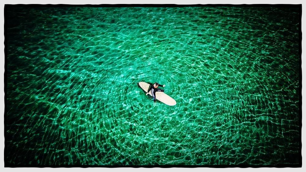 Aerial view of a surfer girl waiting for a wave at a paradise beach in Galicia, Spain. (@andresgarciam) #yachtry #luxury #charters #sailor