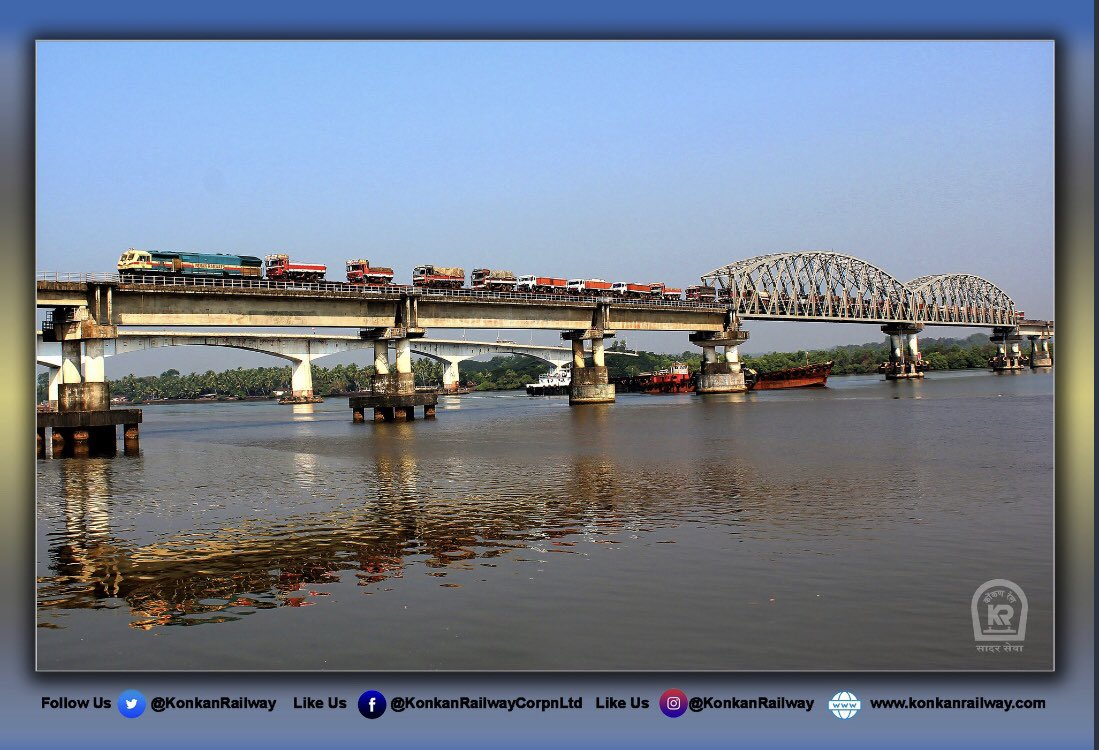 Spectacular view of Ro-Ro (Roll On - Roll Off) train passing on the structural wonder, Zuari river bridge over Konkan Railway route. In this arrangement trucks are loaded on BRN wagons.The driver and cleaner of the truck travel along, sleeping in their truck cabin.