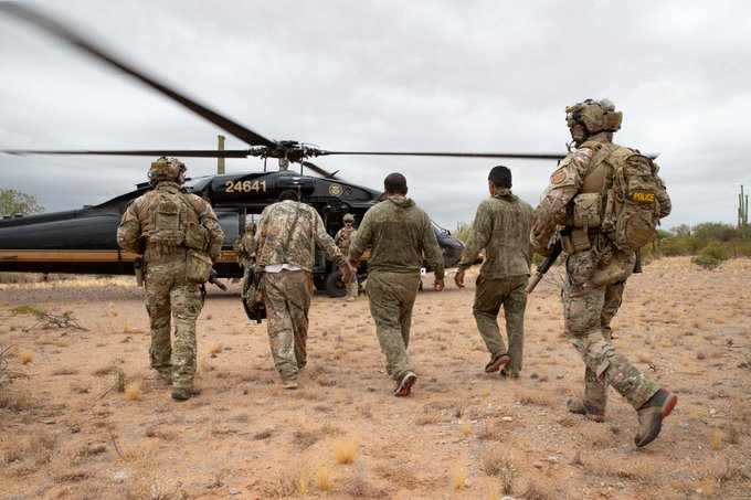 Tucson Sector Border Patrol agents escorting illegal aliens to a CBP helicopter in the remote desert East of Why, AZ
