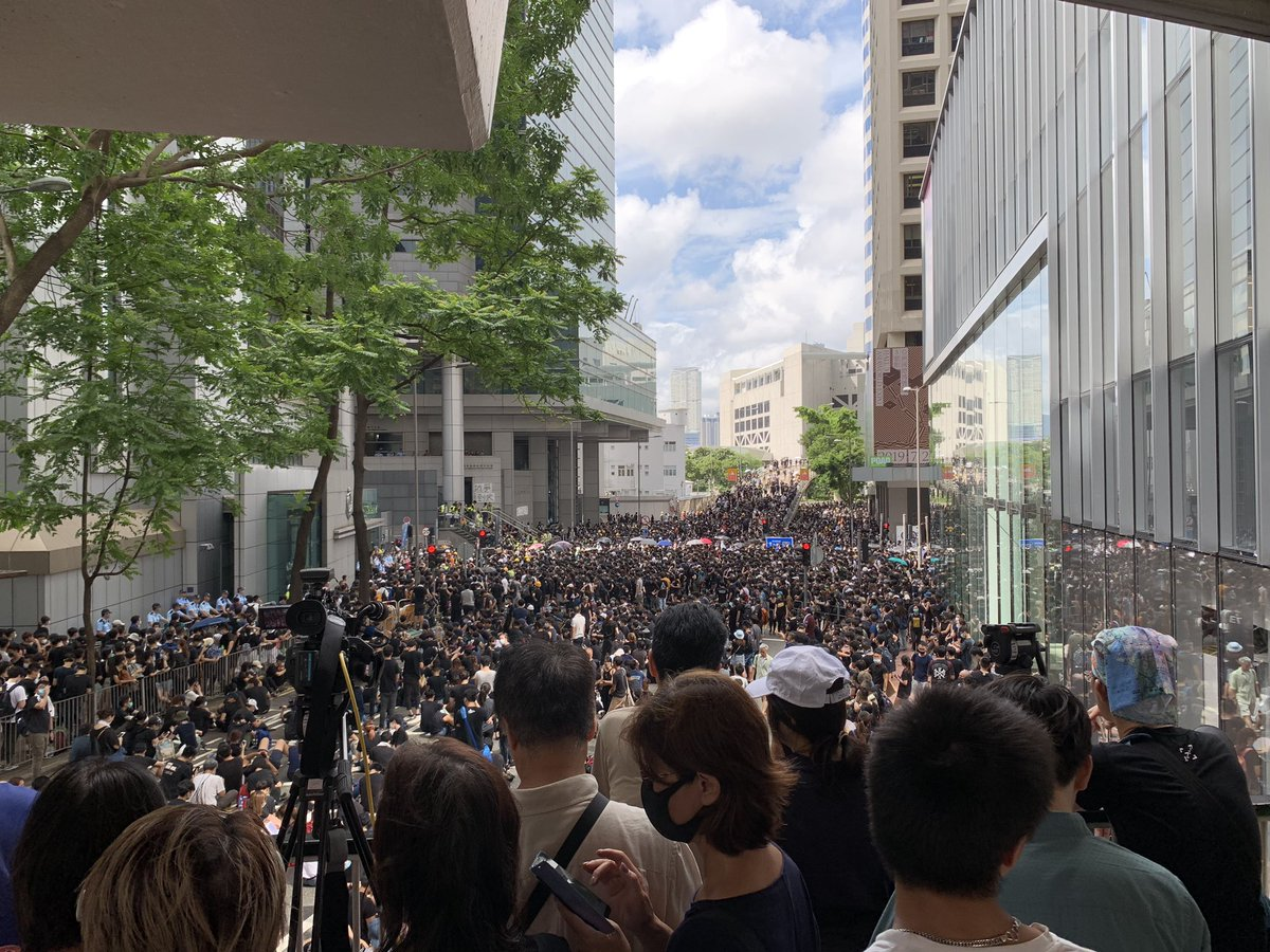 There are still people streaming in to join protests outside HK's police HQ. Luckily for all involved, the street is in shade right now. It's really 32c with 72% humidity #ExtraditionBill