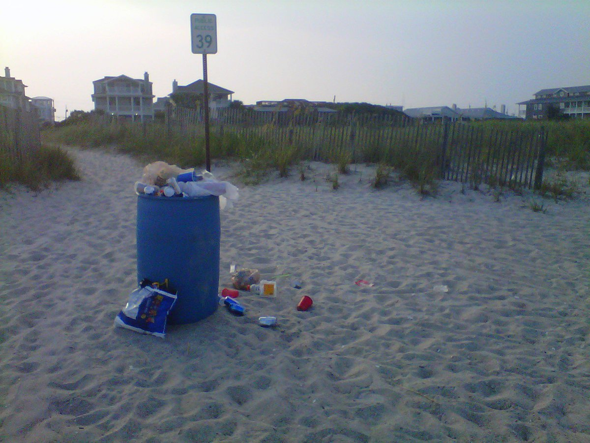 An overflowing trash can on a beach.