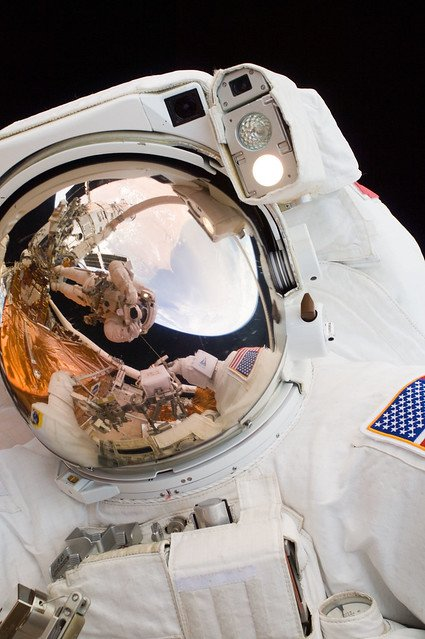 Its #NationalSelfieDay! 📸 In this close-up scene featuring John Grunsfeld (@SciAstro) performing a spacewalk to work on Hubble, the reflection in his helmet visor shows Andrew Feustel (@Astro_Feustel) taking the photo perched on the end of the robotic arm during SM-4.