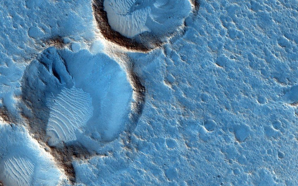 Imagen de la cámara HiRISE de Mars Reconnaissance Orbiter muestra cráteres  y depósitos de viento en el sur de Acidalia Planitia. Para el ojo humano el área probablemente se vea gris y rojiza. Crédito de la imagen: HiRISE, MRO, LPL (U. Arizona), NASA https://apod.nasa.gov/apod/astropix.html…