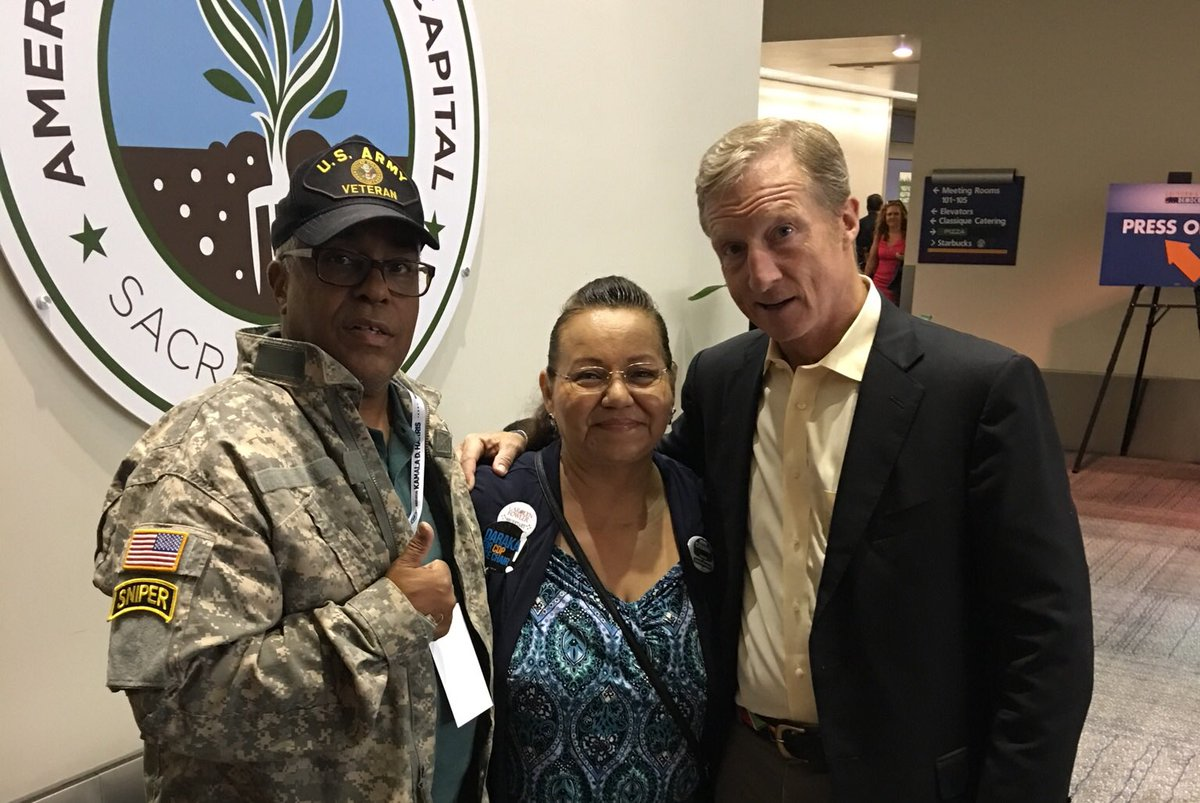 Tom Steyer, right, poses for a photo with Basil Kimbrew and Kimbrew's wife, Lizet. (Courtesy of Basil Kimbrew)