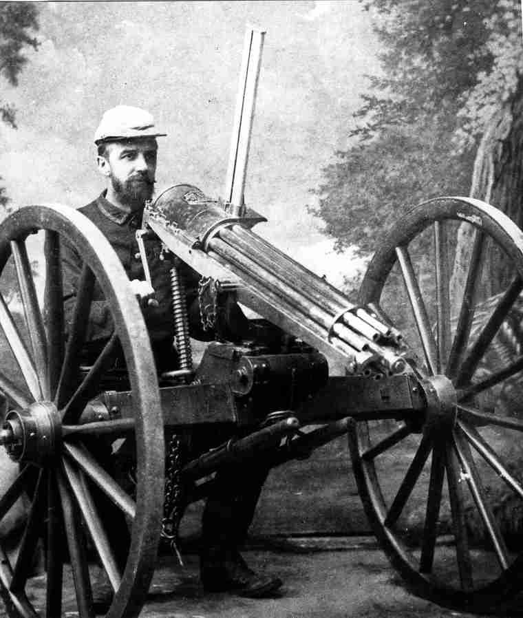 'Lt. Arthur Howard posing with a Gatling gun used in Northwest Resista...