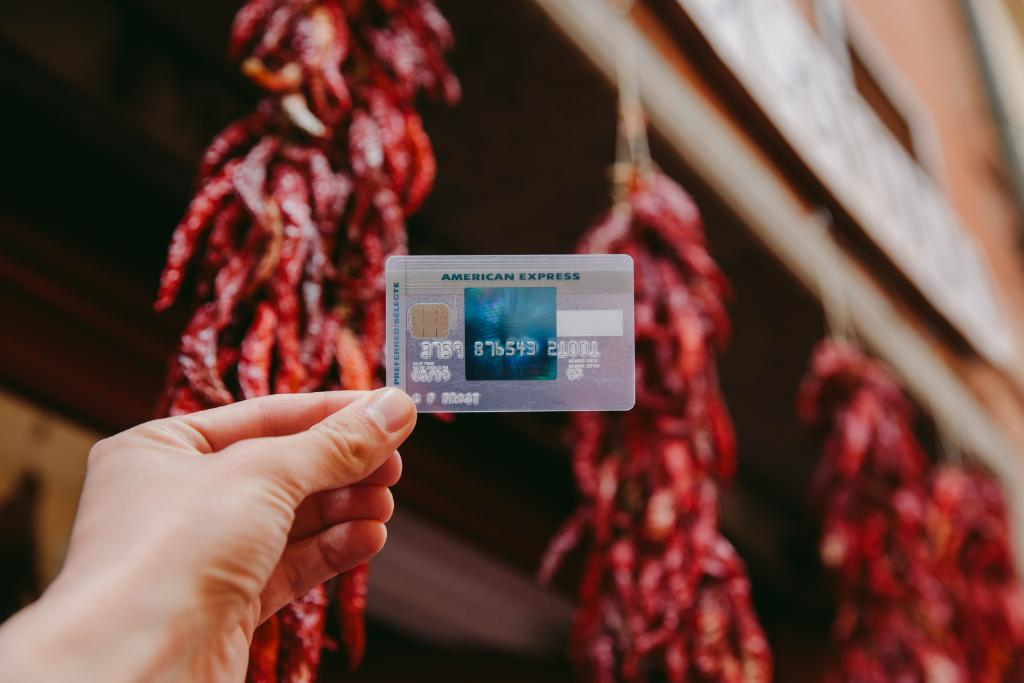 The SimplyCash Preferred Card from American Express against a background with a store with strands of red chili peppers on display. In the picture, you can see the characteristic transparency of the card