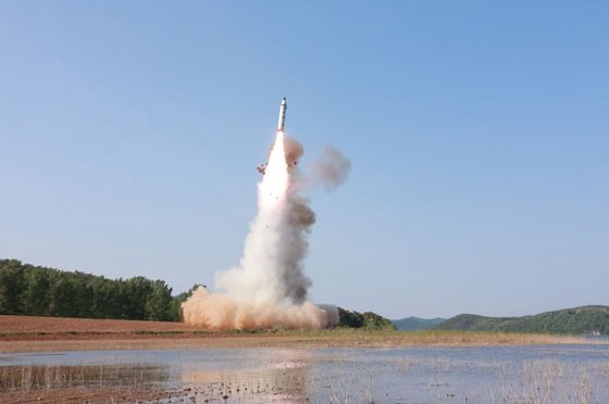 The photo shows a ballistic  missile test of North Korea's Pukguksong-2, as the missile takes off with a trail of smoke behind it. It is pictured near some hills and rural land.