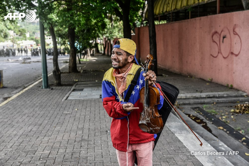 Wuilly Arteaga, who has protested peacefully by playing classical music during the violence in Venezuela, holds his broken violin