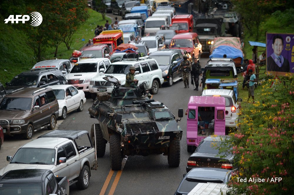 A Philippine military convoy gets stuck in traffic as residents of southern city of Marawi flee ongoing battle with Islamist militants