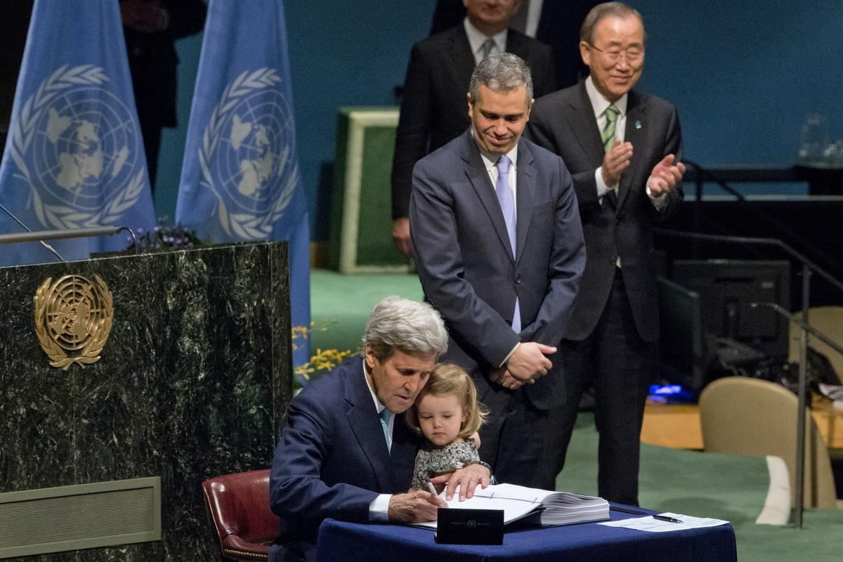 In a different political era — just 13 months ago — John Kerry went to the UN, held his granddaughter tight, and signed the Paris agreement.