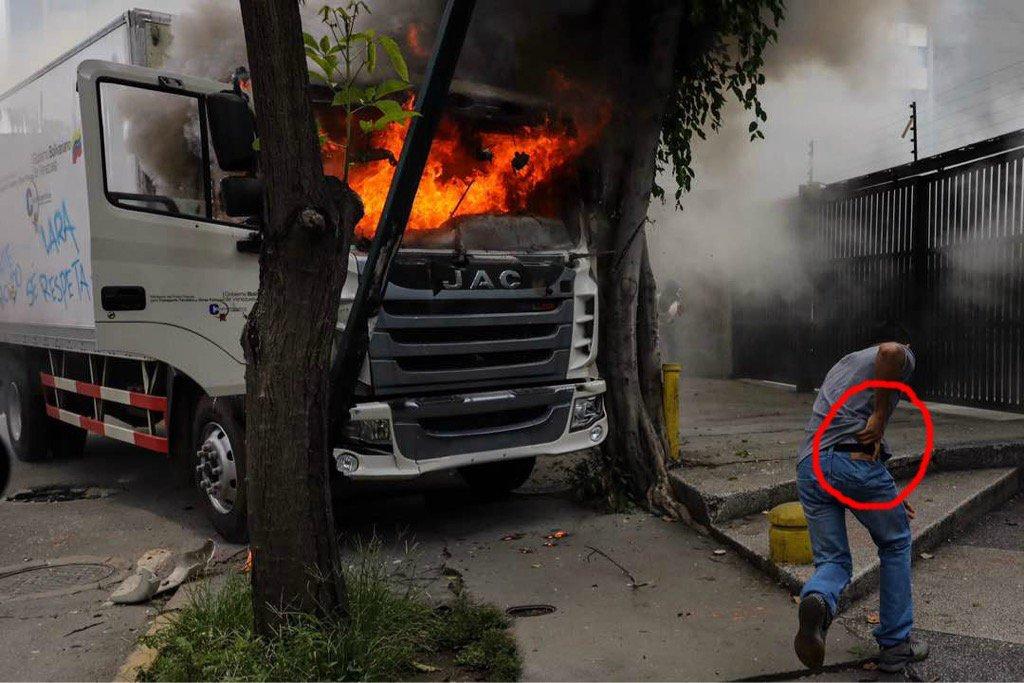 Vean a civil artado intentando sacar presunta pistola durante quema camión del MinTransporte vía  @mgutierrezphoto