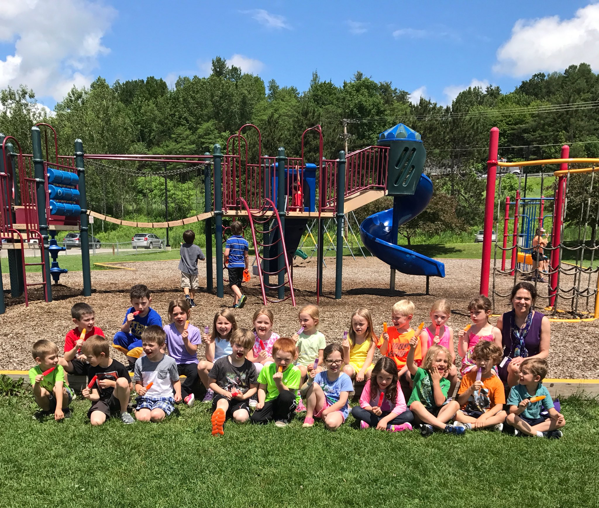 image of a group of students posing in front of the playground