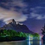 タヒチ、ボラボラ島の中央にそびえるオテマヌ山。山にかかる笠雲が月光と村の灯りに照らされていました。(…