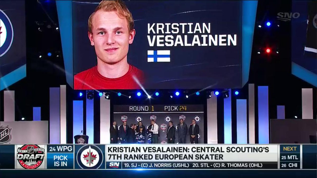 Kristian Vesalainen pulls on a Winnipeg Jets sweater for the first tim...