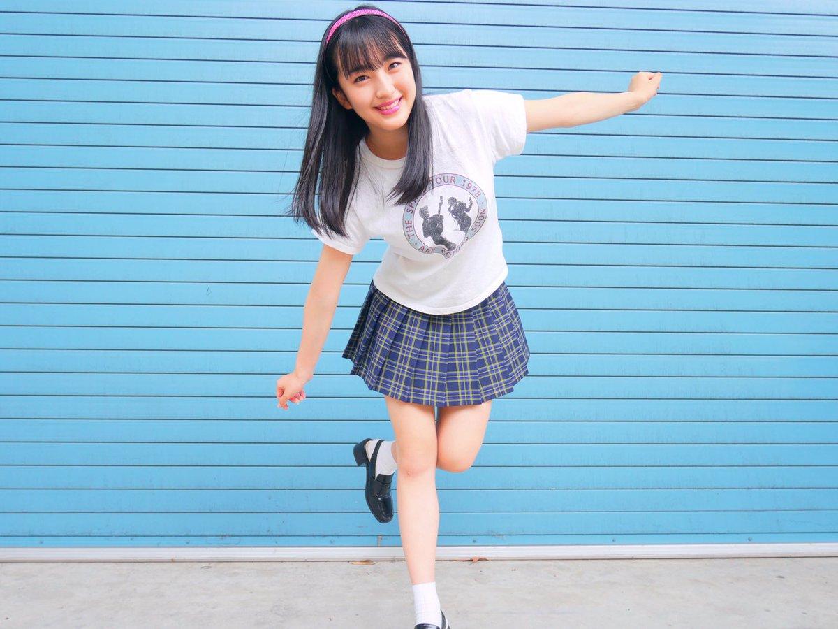 チェックの制服スカートにTシャツを合わせ片足で立つHKT48の田島芽瑠